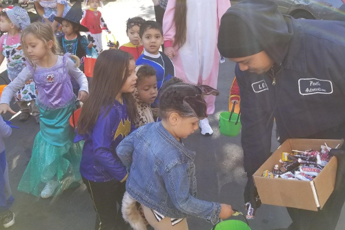 Handing out Halloween candy to the local preschoolers, outside the shop